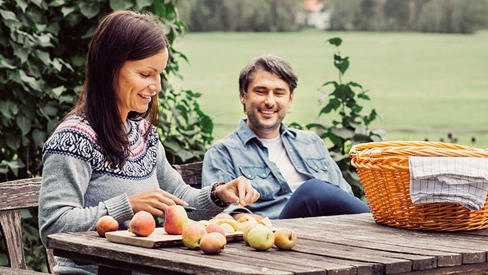 A woman and man sit at an outdoor table slicing pears.