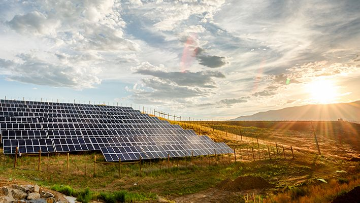 Solar panels sit out in a field as the sun rises above a mountain.