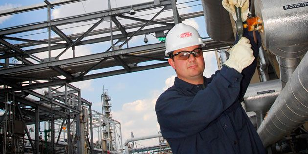 Man with safety glasses working in an industrial setting.