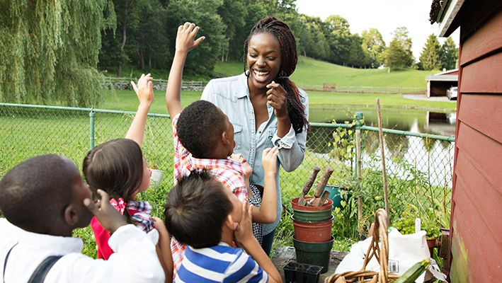 A young woman laughs as she teaches children about gardening.
