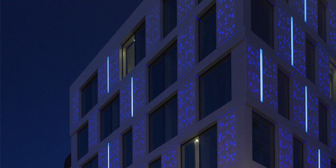 The new Motel One building by Mackay + Partners in the historic Minories neighbourhood of the City of London features an illuminated façade made from DuPont™ Corian® high-tech surface. Photography courtesy of Mackay + Partners, all rights reserved.