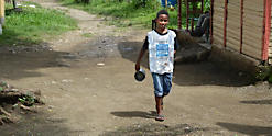 Boy carrying cup for water
