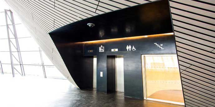 Wall cladding in DuPont™ Corian® in ultra black Deep Nocturne made with innovative DeepColour™ Technology, creates a sleek, seamless finish in the lift lobby of the 'legacy mode' Aquatics Centre by Zaha Hadid Architects. Photo courtesy of Cutting Edge, all rights reserved.