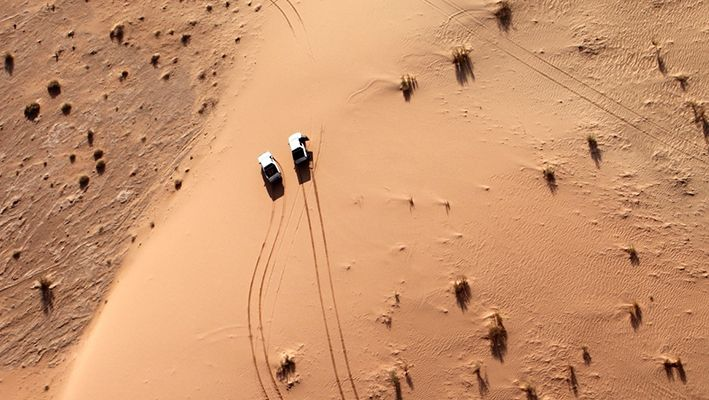 Aerial shot of two jeeps driving through the desert.
