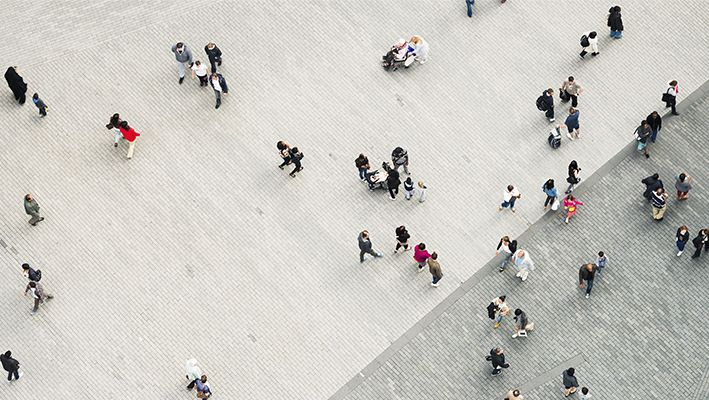 Aerial view of people walking across a bricked plaza.