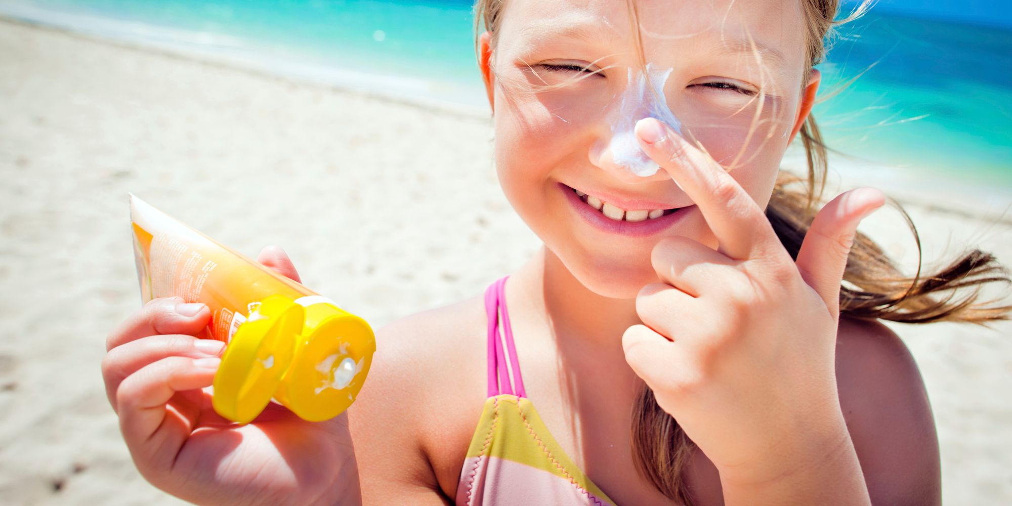 A girl applies sunscreen from a polyethylene tube.