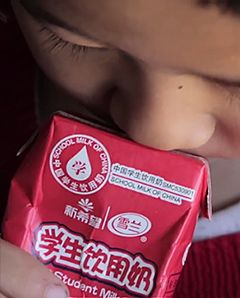 A close up shot of a child's face as they drink from a juice box.