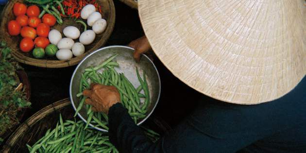 A vendor in Hoi An, Vietnam sells locally grown, fresh produce at a food market.