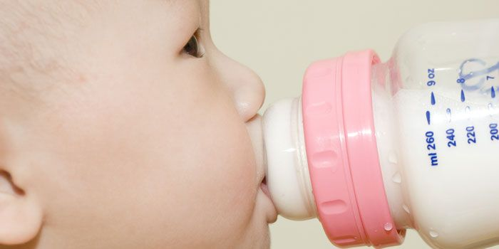 Child drinking formula from bottle