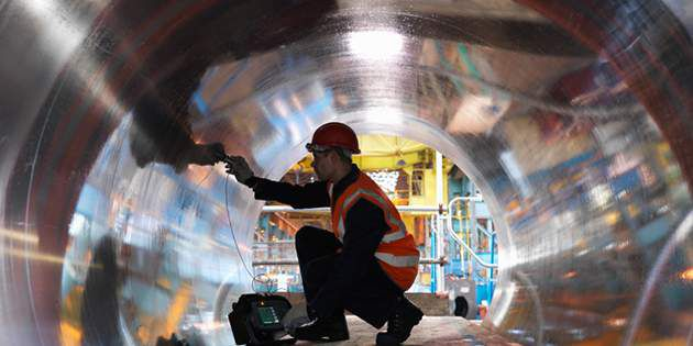 A line worker examines a massive pipe while following process safety management