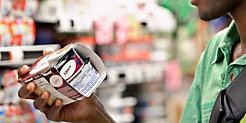 A shopper picks up a package of yogurt.