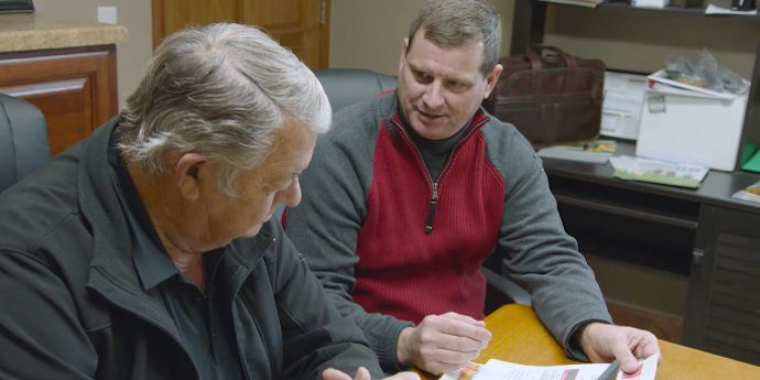 Local DuPont team member consults with Iowa corn grower Jim Peterson about his corn yield goals